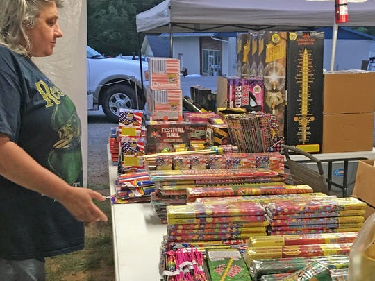 American Legion Post 248 Assistant Adjutant Shari Lewis straightens up the display at the Fairview fireworks tent.