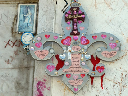 "Voodoo fans mark an ""x"" one or more times at the grave of Marie Laveau, in hopes their hopes will be addressed."