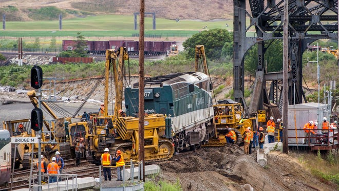 Crews put a derailed Amtrak locomotive back on the tracks Monday, July 3, 2017, in Steilacoom next to the bridge over Chambers Creek, Wash.