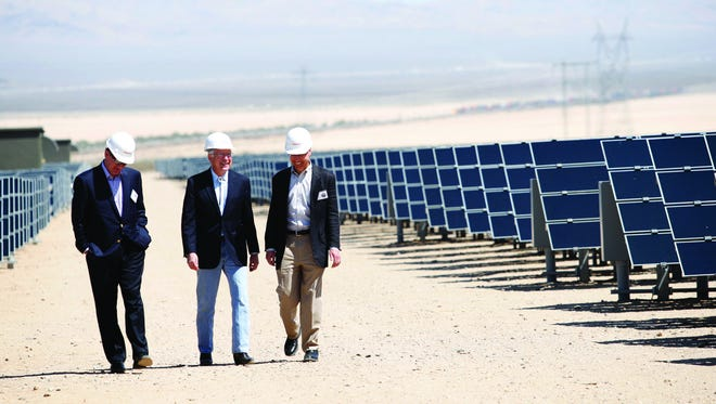 From left, Al Monaco, president of Enbridge, U.S. Interior Secretary Ken Salazar and Frank De Rosa, a senior vice president of First Solar tour the Enbridge Silver State North Project solar facility in the Ivanpah Valley near Primm, Nev. Regulators are meeting to determine whether or not to hold off on rate hikes for net metering customers.