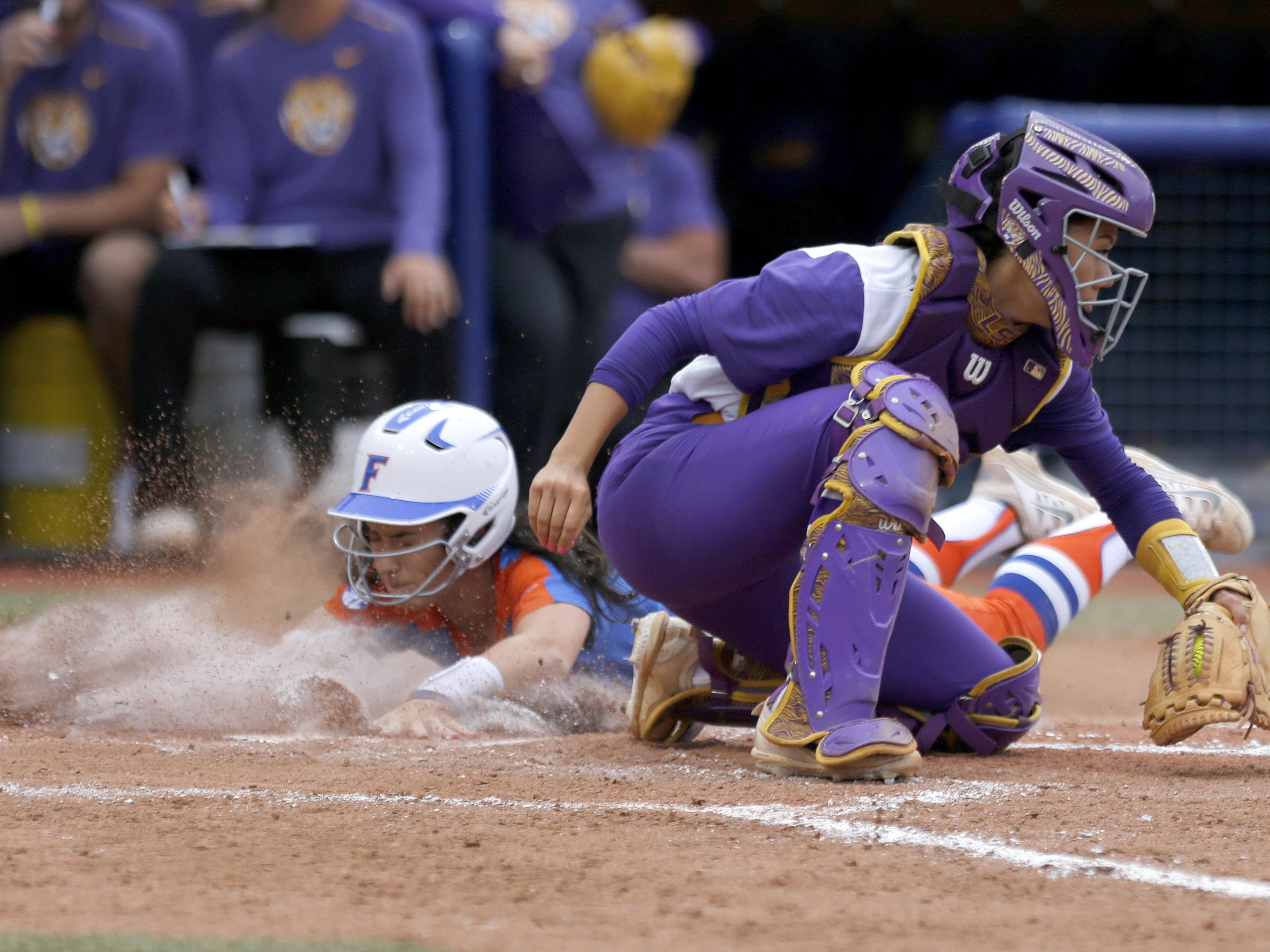 Florida's Alex Voss (0) slides into home as LSU's Sahvanna Jaquish (2) waits to apply a the tag in the fourth inning during the Women's College World Series softball game in Oklahoma City, Friday.