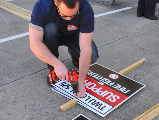 Firefighter/driver Markevan Swenson builds signs outside