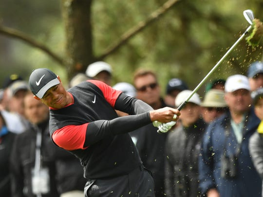 Tiger Woods hits from the fairway on the 1st hole during the final round of the Masters on April 8,