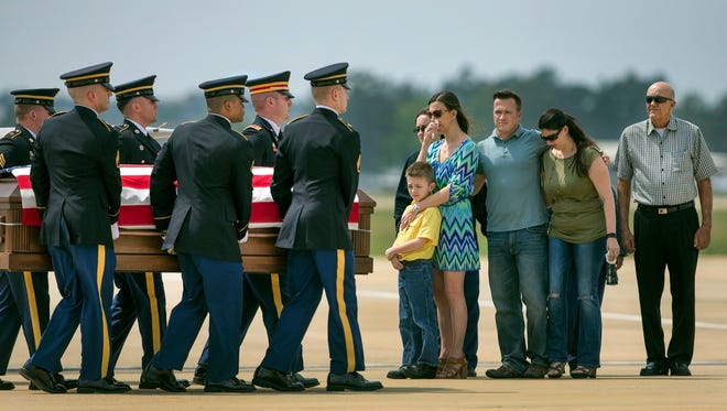 The family, right, of Chief Warrant Officer Four George Wayne Griffin Jr., huddles together as his casket passes by after arriving by plane to the Louisiana National Guard Army Aviation Support Facility in Hammond, Louisiana on Saturday, March 21, 2015. (AP Photo/NOLA.com The Times-Picayune, Chris Granger)