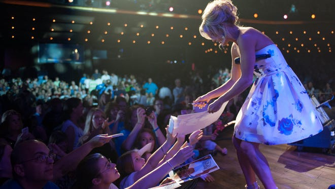 Carrie Underwood signs autographs for fans at the Grand Ole Opry. She will play four shows at the Opry on Friday and Saturday.