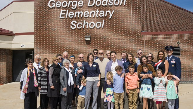 A group of students, staff and parents stand in front of Dodson Elementary School, which will be one of the first schools impacted by the passage of the March bond proposal passage.