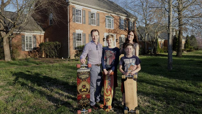 Julian Moffett, Dylan Moffett, Nina Moffett and Jonah Moffett stand in front of their home in Nashville. The Moffetts, who recently relocated from Switzerland, enjoy longboarding as a family.