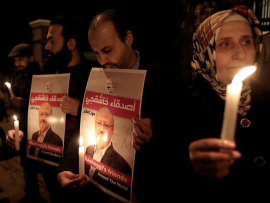 Protestors hold candles and pictures of Jamal Khashoggi