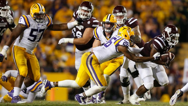 Mississippi State Bulldogs running back Josh Robinson (13) runs as LSU Tigers safety Ronald Martin (26) pursues during the second half of a game at Tiger Stadium. Mississippi State defeated LSU 34-29.