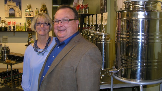 """Amy Jo and Curt Campbell pose in The Oilerie olive oil bar at Urban Edge shopping center in Suamico. Curt Campbell, founder and CEO of The Oilerie, appeared on the ABC program """"Shark Tank."""" His episode will air Friday."""