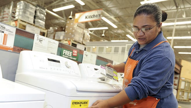 Plumbing associate Marlynn Mobel points to the EnergyGuide posted on an energy-efficient top-load washer at The Home Depot in Tamuning in this January 2013 file photo. According to a publication from the U.S. Commerce Department's Technology Education, household appliances, such as washers, can be susceptible to power surges.
