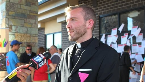 The Rev. Benjamin Hutchison discusses with the media what he says was a forced resignation from Cassopolis United Methodist Church after church leaders asked about his same-sex partner, on Tuesday, July 28, 2015 in  Lansing, Mich. United Methodist clergy and churchgoers held a news conference outside the bishop's office in support of Hutchison, an openly gay pastor who says he was forced to resign.