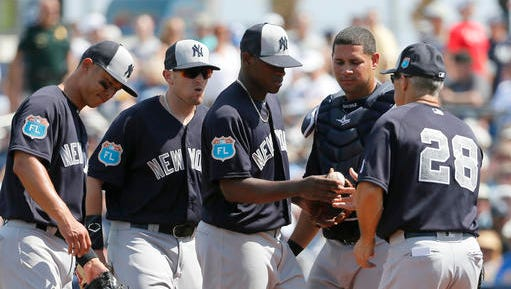 New York Yankees starting pitcher Luis Severino turns the ball over to manager Joe Girardi (28) in the fourth inning of a spring training baseball game against the Tampa Bay Rays on Saturday, March 12, 2016, in Port Charlotte, Fla. (AP Photo/Tony Gutierrez)
