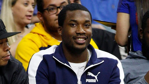 In this Wednesday, Feb. 3, 2016, photo, rapper Meek Mill looks on during the second half of an NBA basketball game between the Atlanta Hawks and the Philadelphia 76ers in Philadelphia. A Wallingford, Connecticut police spokeswoman said that officers responded to reports of shots fired outside the Oakdale Theatre after rapper Meek Mill performed. Officers found two dead and say the other two with non-life-threatening injuries were taken to hospitals.