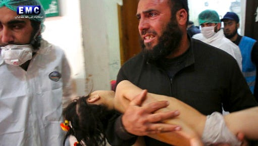 FILE -- In this Tuesday April 4, 2017 file photo, provided by the Syrian anti-government activist group Edlib Media Center, that is consistent with independent AP reporting, shows a man carrying a child following a suspected chemical attack, at a makeshift hospital in the town of Khan Sheikhoun, Syria. Turkey's health minister, Recep Akdag said Tuesday, April 11, 2017, that test results conducted on victims of the chemical attack in Khan Sheikhoun confirm that sarin gas was used.