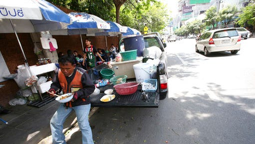 In this April 7, 2017 photo, a motorcycle taxi driver eats noodles at a street food stall during his lunch on Thonglor road in Bangkok, Thailand. Officials see street food as an illegal nuisance and have warned hawkers in Thonglor to clear out by April 17. Efforts by authorities in military-ruled Thailand to impose order on the chaotic capital city have a fresh target: cheap and tasty pad thai. The latest crackdown by Bangkok city officials is going after the vendors whose carts selling everything from Thailand's signature noodles to spicy tom yum goong soup have become institutions on the capital's hot and humid sidewalks.