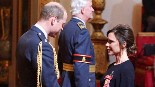 Fashion designer Victoria Beckham, right, receives her OBE from Britain's Prince William, the Duke of Cambridge during an investiture ceremony at Buckingham Palace in London, Wednesday April 19, 2017.