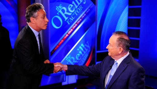 """FILE - In this Sept. 22, 2010 file photo, Jon Stewart, from Comedy Central's """" """"The Daily Show with Jon Stewart,"""" left, shakes hands with Bill O'Reilly during the taping of a segment on """"The O'Reilly Factor,"""" on the FOX News Channel, in New York."""