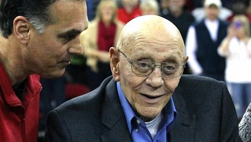 FILE - In this March 1, 2014, file photo, Jerry Tarkanian is escorted by his son, Danny, during halftime ceremonies honoring the former basketball coach at Fresno State University in Fresno, Calif. The Hall of Fame basketball coach is hospitalized in Las Vegas, where his son says he's being treated for pneumonia.