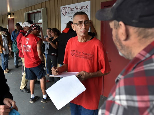 """J. R. Gonzalez (center), a retired volunteer at The Source, an outreach ministry in Indian River County, registers another homeless person for an afternoon lunch on Tuesday, Jan. 2, 2018, at their office at 1015 Commerce Avenue in Vero Beach. """"People are in need, they are living in the woods, out on the streets, sleeping on benches,"""" Gonzalez said. """"This organization believes in helping the poor so that's what we do all day long."""""""