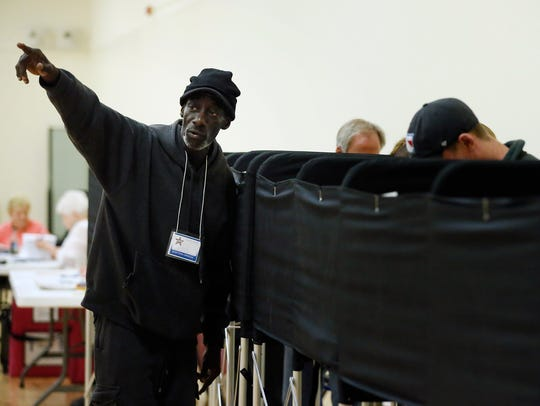 An election worker points to the area of a machine