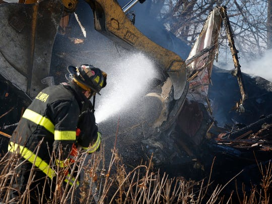 Firefighters spray water on debris as it's dropped into a pile in the front yard of 326 West Ave. on Elmira's Southside Tuesday.