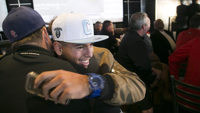 Centennial High defensive end and tight end Andrew Nichols hugs his youth football coach John Drago, after Nichols announced he will be attending Columbia University to play football during National Signing Day at Majerle's Sports Grill in Phoenix on Wednesday, February 1, 2017.