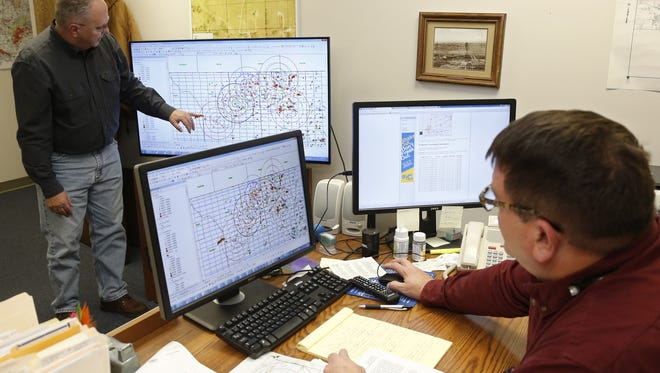 Charles Lord, left, senior hydrologist, explains the mapping procedure used by the Corporation Commission to chart fault lines, earthquakes and disposal wells, as Jim Marlatt, right, Oil & Gas Specialist, looks on from his desk, in Oklahoma City on Nov. 30, 2015.