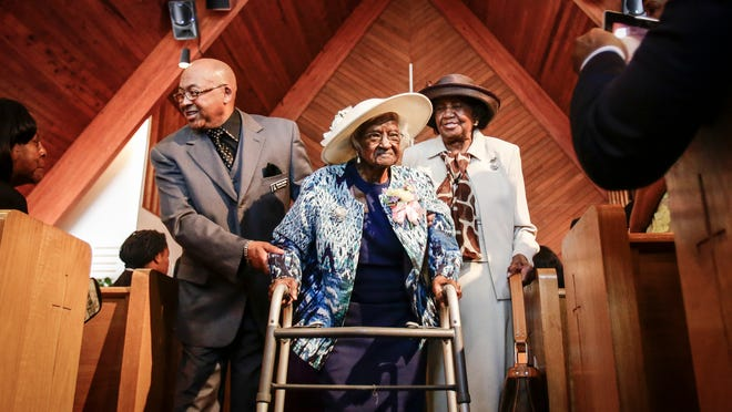 Deacon Charles Smith, of Belleville, left, and church charter member Willa Williams, of Inkster, right, help escort Jeralean Talley, then 115 to the reception in her honor at the New Jerusalem Baptist Church in Inkster on May 25, 2014.
