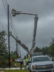 Gulf Power crews restore power to a home in Navarre Beach on Sunday, Oct. 8, 2017.