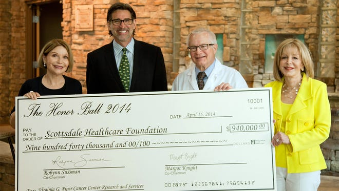 2014 Honor Ball co-chairs Margot Knight and Robynn Sussman present a check for $940,000 from event proceeds to Mark Slater, chief executive of Scottsdale Healthcare Research Institute, and Dr. Daniel Von Hoff, chief scientific officer for Virginia G. Piper Cancer Center Clinical Trials at Scottsdale Healthcare.