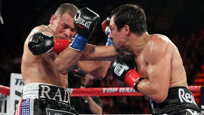 Four-division champion Juan Manuel Marquez, right, connects to the jaw or Mike Alvarado on his way to a 12-round unanimous decision victory Saturday.