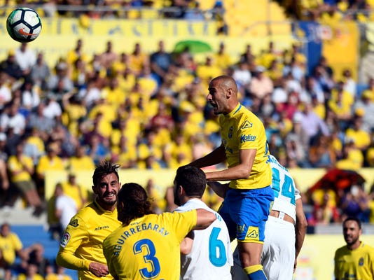 Las Palmas' Alejandro Galvez, top, jumps above Real Madrid's Nacho, center, and Casemiro during a Spanish La liga soccer match between Las Palmas and Real Madrid at the Gran Canaria stadium on the Canary island of Las Palmas, Spain, Saturday March 31, 2018. (AP Photo/Lucas de Leon)