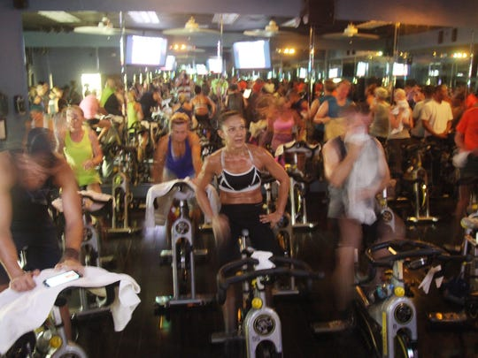 A wide variety of professionals are among 30-40 participants in the early morning spin class at Around The Clock Fitness in Fort Myers.