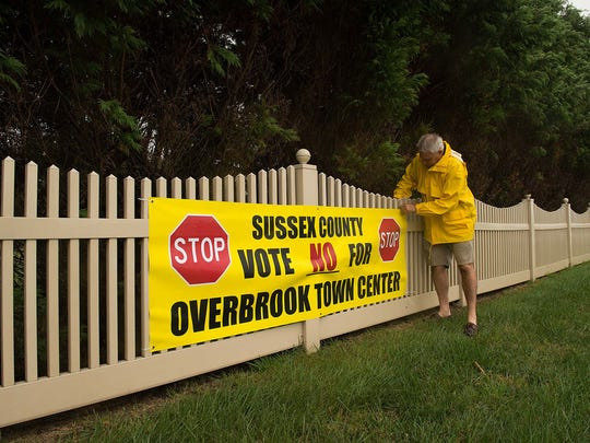 Rich Borrasso straightening the sign to vote no for Overbrook Town Center across from the development Red Fox Run in Milton on Thursday Sept. 25, 2014.