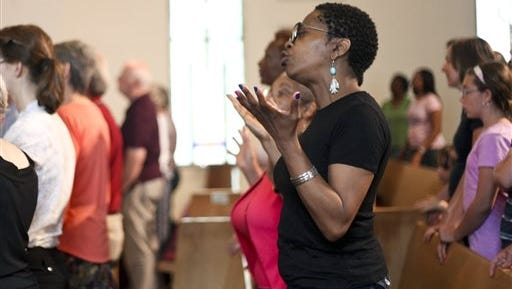 People attend a service in remembrance of the nine people killed in Charleston, S.C., Wednesday, June 24, 2015, at the African Methodist Episcopal Church in Kalamazoo, Mich. (Daytona Niles/Kalamazoo Gazette-MLive Media Group via AP) ALL LOCAL TELEVISION OUT; LOCAL TELEVISION INTERNET OUT