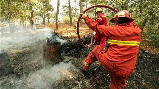 Elgin firefighter Thomas Pritchett, left, and Smithville Capt. Adrian Sepulveda, right, climb over burning debris and tree as they move a fire hose closer to the fire as they fight the Hidden Pines Fire burning at the end of Keller Road near Smithville, Texas, Wednesday, Oct. 14, 2015. The Texas A&M Forest Service says challenging topography and uncontrolled fire lines has slashed the containment of the Bastrop County fire to 10 percent as night fell Wednesday. The Forest Service had estimated 50 percent containment earlier Wednesday.  Officials say rain has extinguished much of the wildfire that was burning in the Sipsey Wilderness of northwest Alabama.