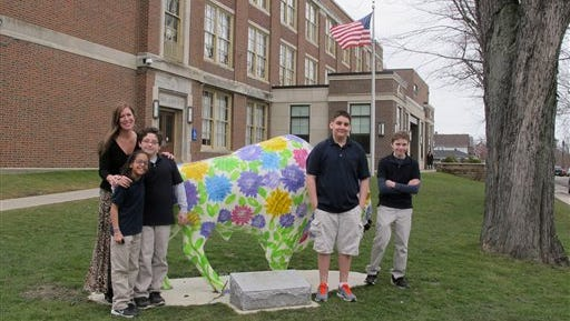 In this Feb. 29, 2016 photo, teacher Kelly Gasior, left, and students, from left, Olivia Mashtaire, Ryan Lysek, Christian Vazquez and Tyler Lysek stand with a statue of a Buffalo that's been emblazoned with anti-bullying messages outside Lorraine Academy, Public School No. 72, in Buffalo, N.Y. Educators in Buffalo and elsewhere worry the name-calling, mocking and social media attacks that have gotten applause in the presidential campaign could undermine schools'  bullying prevention policies that call for kindness and respect. (AP Photo/Carolyn Thompson)