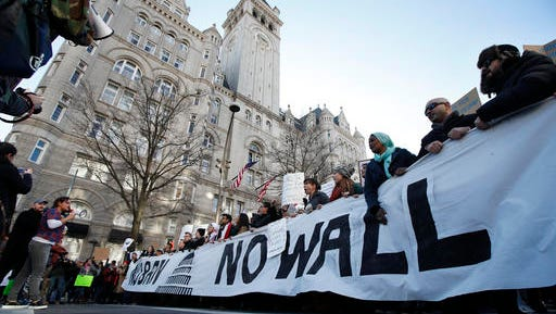 Protesters march along Pennsylvania Avenue past the Trump International Hotel during a rally protesting the immigration policies of President Donald Trump, near the White House in Washington, Saturday, Feb. 4, 2017.