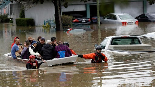 Rescue crews take out residents from a flooded neighborhood Tuesday, Feb. 21, 2017, in San Jose, Calif. Rescuers chest-deep in water steered boats carrying dozens of people, some with babies and pets, from a San Jose neighborhood inundated by water from an overflowing creek Tuesday.