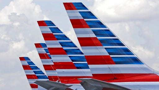 FILE - This July 17, 2015, file photo shows the tails of four American Airlines passenger planes parked at Miami International Airport, in Miami. On Tuesday, March 14, 2017, American said it will offer free meals to everyone in economy on certain cross-country flights starting May 1, 2017. The decision at the world's biggest airline copies Delta Air Lines, which announced a month earlier that it would restore free meals in economy on a dozen long-haul U.S. routes in spring 2017.