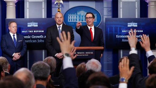 Treasury Secretary Steven Mnuchin, right, joined by National Economic Director Gary Cohn, center, and White House press secretary Sean Spicer speaks in the briefing room of the White House in Washington, Wednesday, April 26, 2017. President Donald Trump is proposing dramatically reducing the taxes paid by corporations big and small in an overhaul his administration says will spur economic growth and bring jobs and prosperity to the middle class.