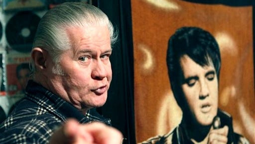 """Paul MacLeod stands before a poster of Elvis Presley in the antebellum home and a private Elvis Presley museum he calls """"Graceland Too,"""" in Holly Springs. MacLeod, a lifetime Elvis fanatic, was found dead on the porch of his home early July 17, two days after authorities say he shot and killed a man who forced his way into the attraction."""