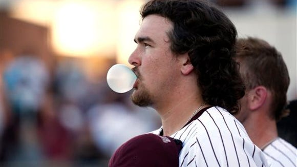 Mississippi State baseball pitcher Jonathan Holder blows a bubble during the playing of the National Anthem prior to their game against Central Arkansas in the NCAA Tournament  in Starkville, Miss., on June 3, 2013.