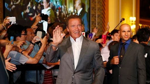 """Arnold Schwarzenegger waves on the red carpet for the Macau premiere of his movie """"The Expendables 3"""" in Macau, China, Friday."""