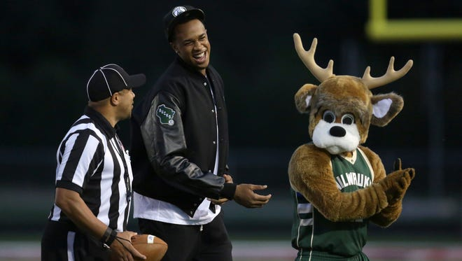 John Henson of the Milwaukee Bucks talks with an official as he leaves the field with Bucks mascot Bango following the coin toss before the Appleton West vs. Appleton East football game at a stop during last year's statewide tour.