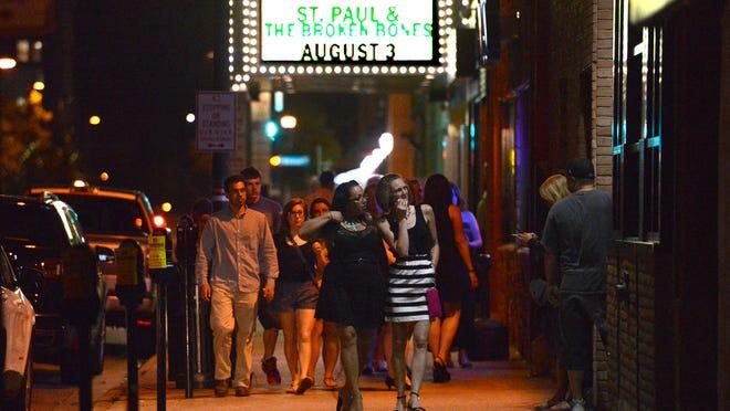 Bar patrons walk alomg S. Washington Street.