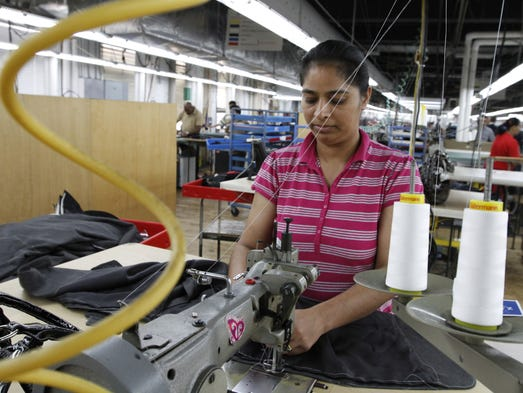 Beljit Kaur, Rochester, sews together panels to pants at Hickey Freeman in Rochester.