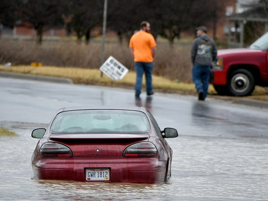 An abandoned car sits deep in water Thursday on North