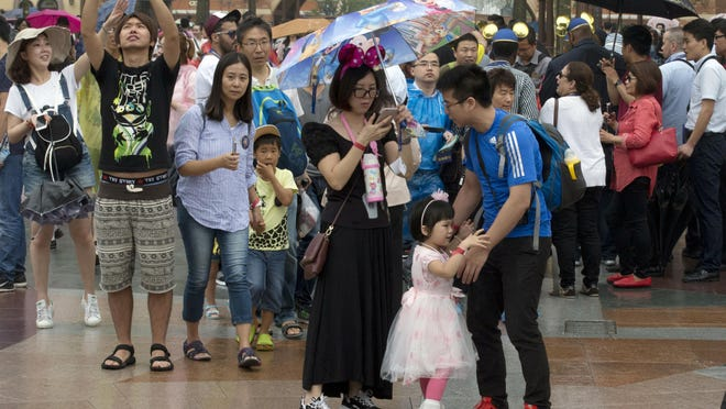 A child asks to be carried during a crowded opening day at the Disney Resort in Shanghai, China, Thursday, June 16, 2016.